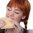 Woman biting into a piece of cheese — Stock Photo