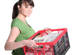 Woman carrying crate of newspapers to be recycled — Stock Photo