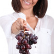 35 years old woman giving a red grape - Stockfoto