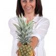 Smiling woman showing pineapple — Stock Photo