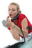 Blond secretary applying lipstick — Stock Photo