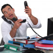 Stock Photo: Office worker trying to answer multiple phones
