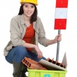 Stock Photo: Female builder kneeling by recycle box