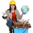 Stock Photo: Womwith globe in hand kneeling by waste materials