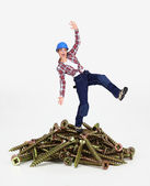 Woman balancing on pile of screws — Stock Photo