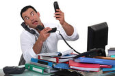 Office worker trying to answer multiple phones — Stock Photo