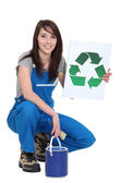 A female painter promoting recycling. — Stock Photo