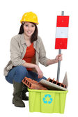 Female builder kneeling by recycle box — Stock Photo