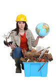 Woman with globe in hand kneeling by waste materials — Stock Photo