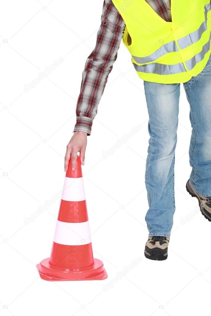 Construction worker putting a traffic cone on the floor — Stock Photo #17107073