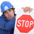 Stock Photo: Builder in jumpsuit holding stop sign