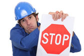 Builder in jumpsuit holding stop sign — Stock Photo