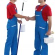 Decorating duo shaking hands — Stock Photo