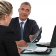 Smiling mature businessman and young blonde assistant — Stock Photo