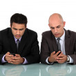 Two businessmen sending text messages — Stock Photo #17122709