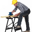 Carpenter using an electric sander - Stock Photo