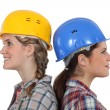 Two female builders standing back to back — Stock Photo #17124877