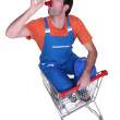 Builder with megaphone sat in shopping trolley — Stock Photo #17125119
