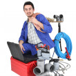 Plumber kneeling with computer — Stock Photo #17125253