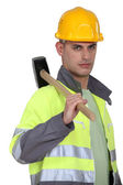 Labourer carrying a mallet — Stock Photo