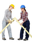 Female builders with a wooden apex — Stock Photo
