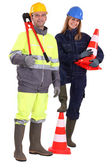 Male and female bricklayers posing with construction cones — Stock Photo