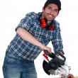 A carpenter with a circular saw. - Stock Photo