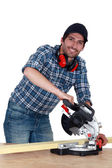 A carpenter with a circular saw. — Stock Photo
