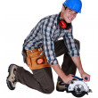 Workman with a circular saw - Stock Photo