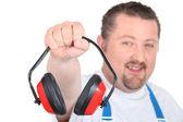Travailleur en salopette bleue miroiter des protections auditives — Photo