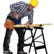 Stock Photo: Msawing plank of wood