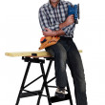 Tradesman sitting on a workbench — Stock Photo #17213195