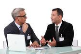 Men chatting at a desk — Stock Photo