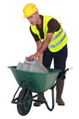 A mason putting breeze blocks in a wheelbarrow. — Foto Stock