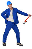 Goofy tradesman holding a pipe wrench — Stock Photo