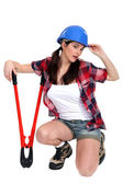 Tired tradeswoman holding clippers — Stock Photo