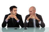 Deux hommes d'affaires assis manger des hamburgers — Photo
