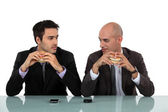 Two businessmen sat eating hanburgers — Stock Photo