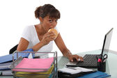 Woman eating sandwich at desk — Stock Photo