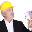 Grey-haired architect holding house made from bank notes — Stock Photo #17344185