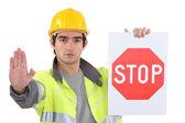 Road arbetstagaren innehar en stoppskylt — Stockfoto