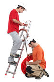 Tradesmen installing copper and corrugated tubing — Stock Photo