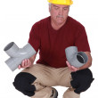 Stock Photo: Plumber choosing part