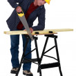 Stock Photo: Tradesmsawing plank of wood