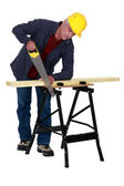Tradesman sawing a plank of wood — Stock Photo