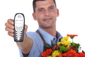 Florist holding forth a telephone — Stock Photo