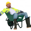 Exhausted builder laying in wheelbarrow — Stock Photo