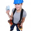 Female electrician holding wedge of cash — Stock Photo #17381707