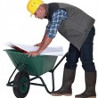 Stock Photo: Tradesmlooking at blueprint while leaning over wheelbarrow
