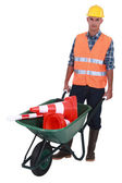 Roadworker with cones in a wheelbarrow — Stock Photo